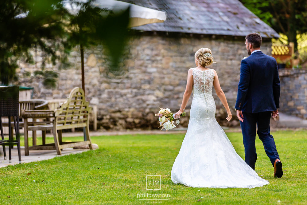 bride and groom walking throuh the ground of pencoed house estat