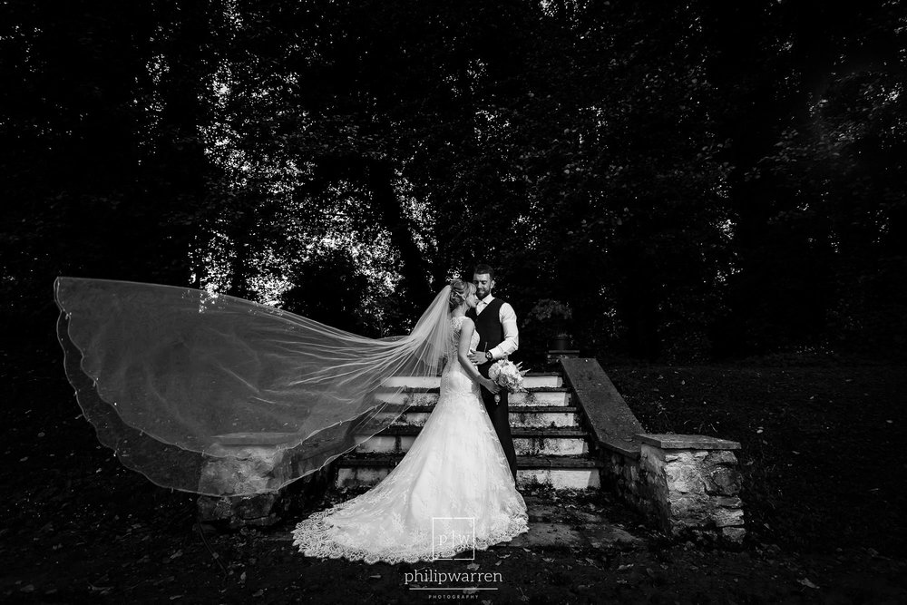 dramatic phot of the bride and groom with the veil blowin the wi