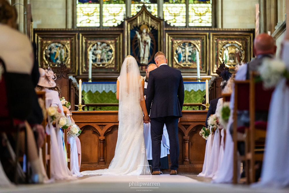 bride and groom in ceremony standing at altar