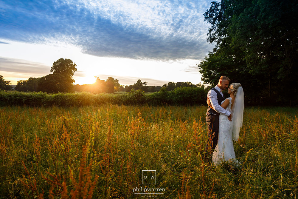 married couple standing in a field at sunset