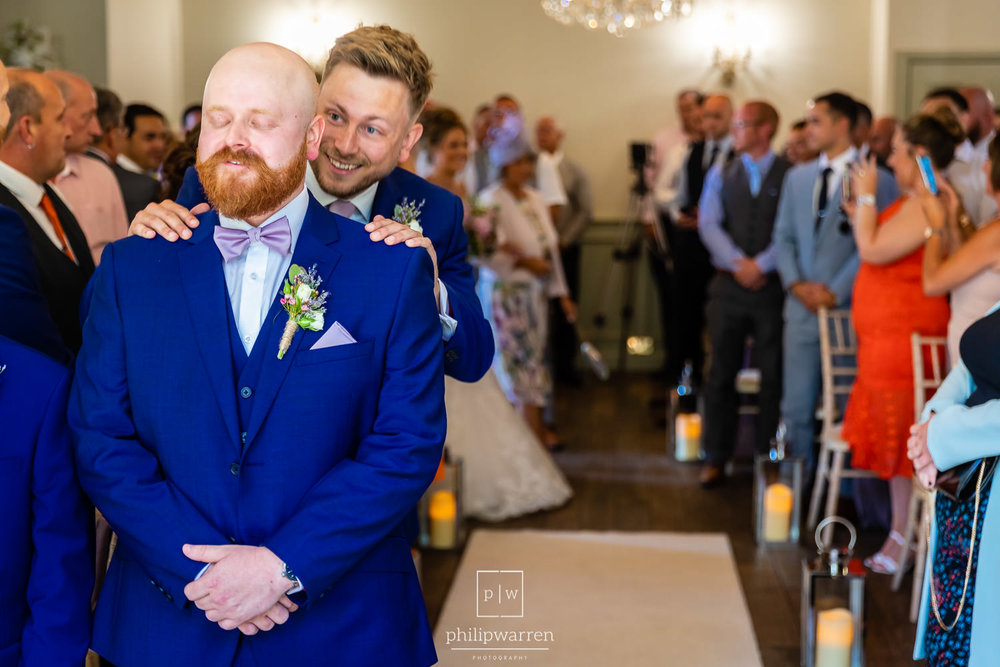 best man laughing at groom as his bride enters the ceremony room