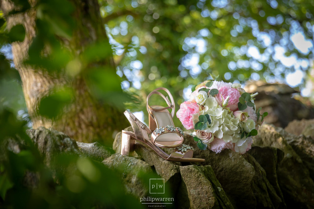 wedding shoes and bouquet on stone wall