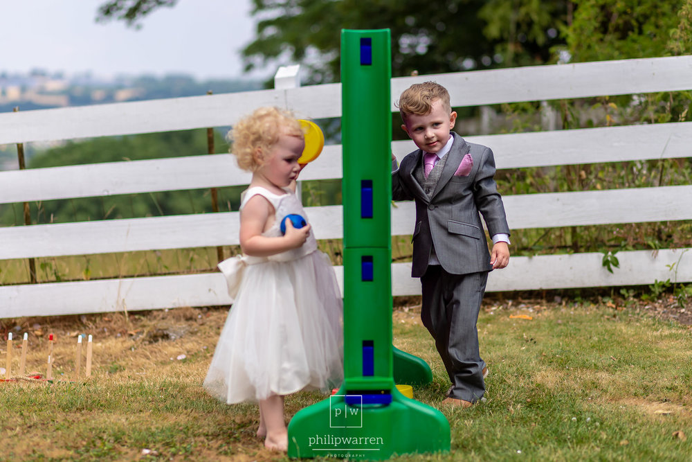 page boy and flower girl playing garden games