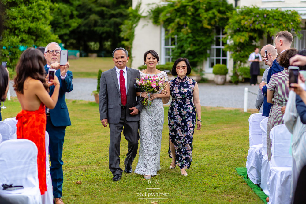 bride walking towards wedding ceremony with her parents