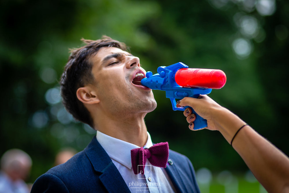 wedding guest squirting alcohol into another guests mout from a