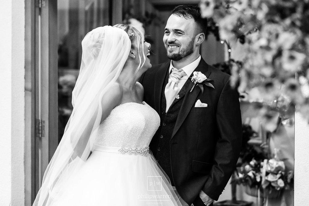 bride and groom smiling outside oldwalls