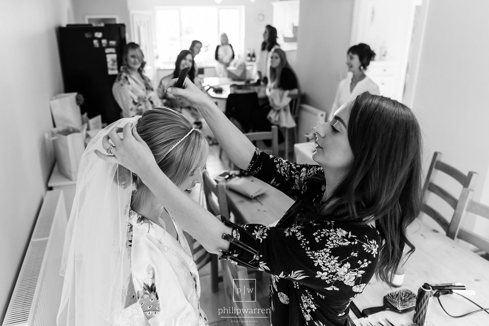 hairdresser putting in veil for bride before wedding