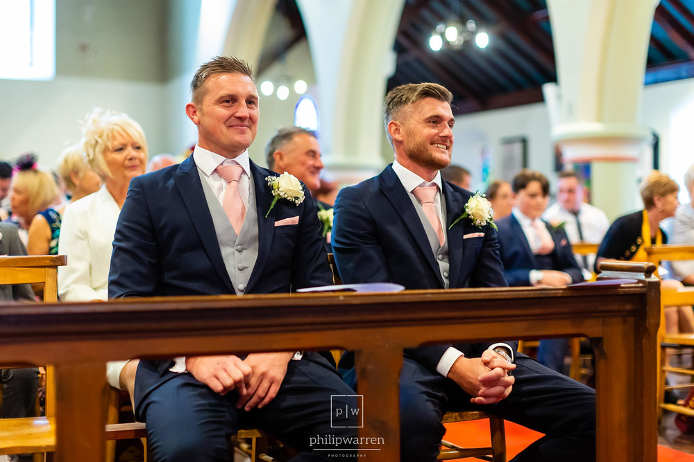 groom and best man sat in the pews of the church smiling