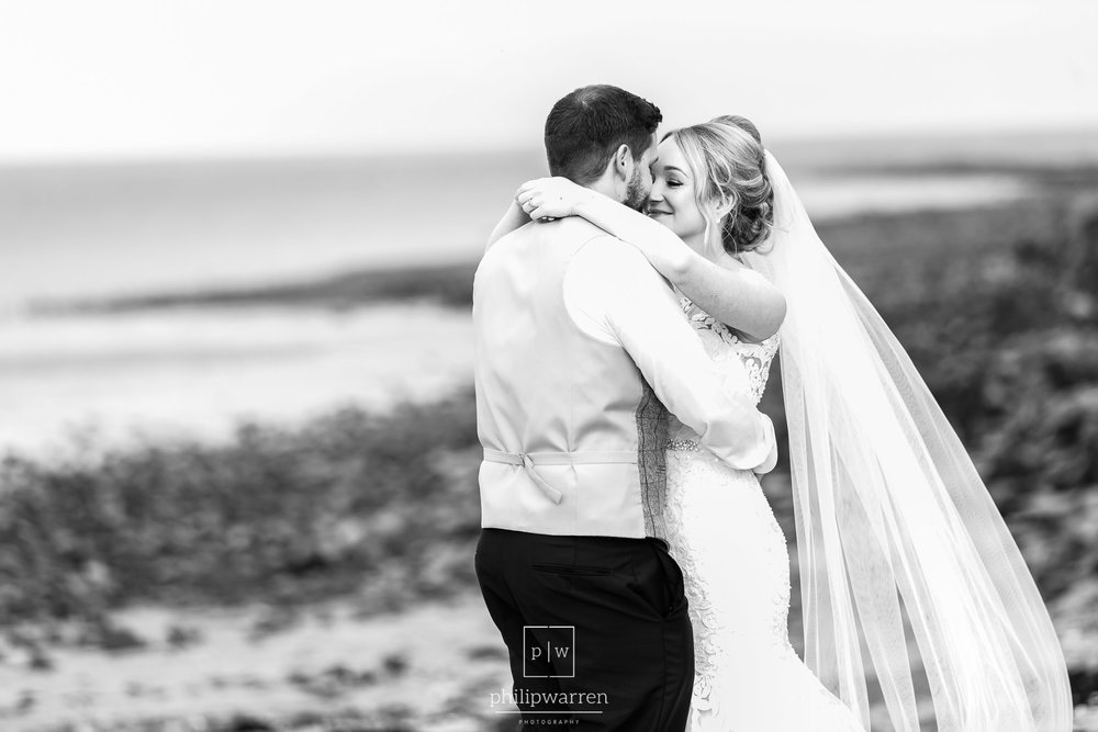 bride and groom hugging on oxwich bay beach