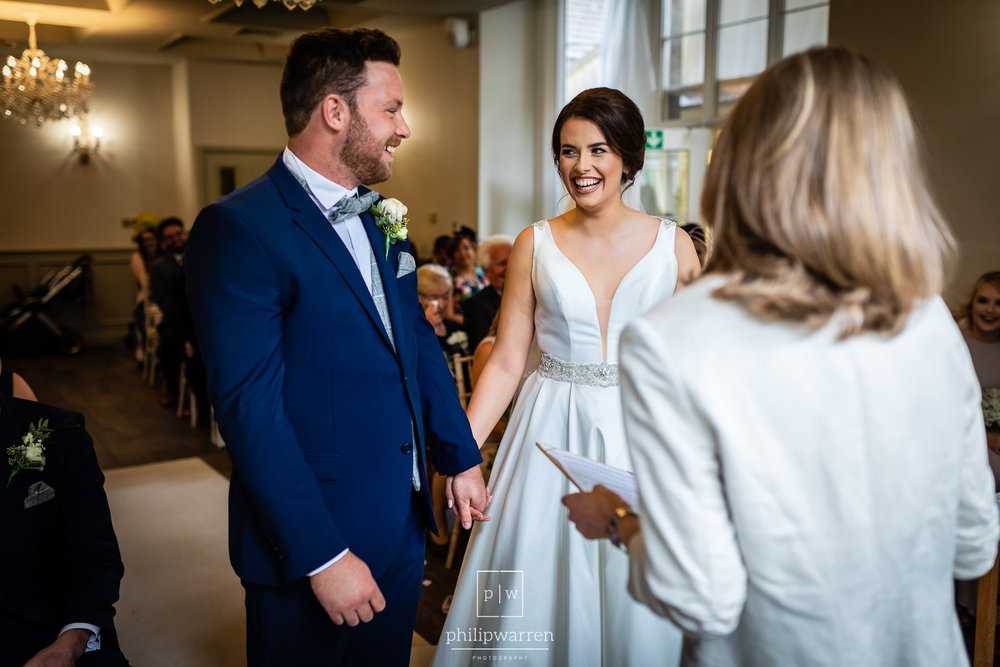 bride and groom laughing at each other during ceremony