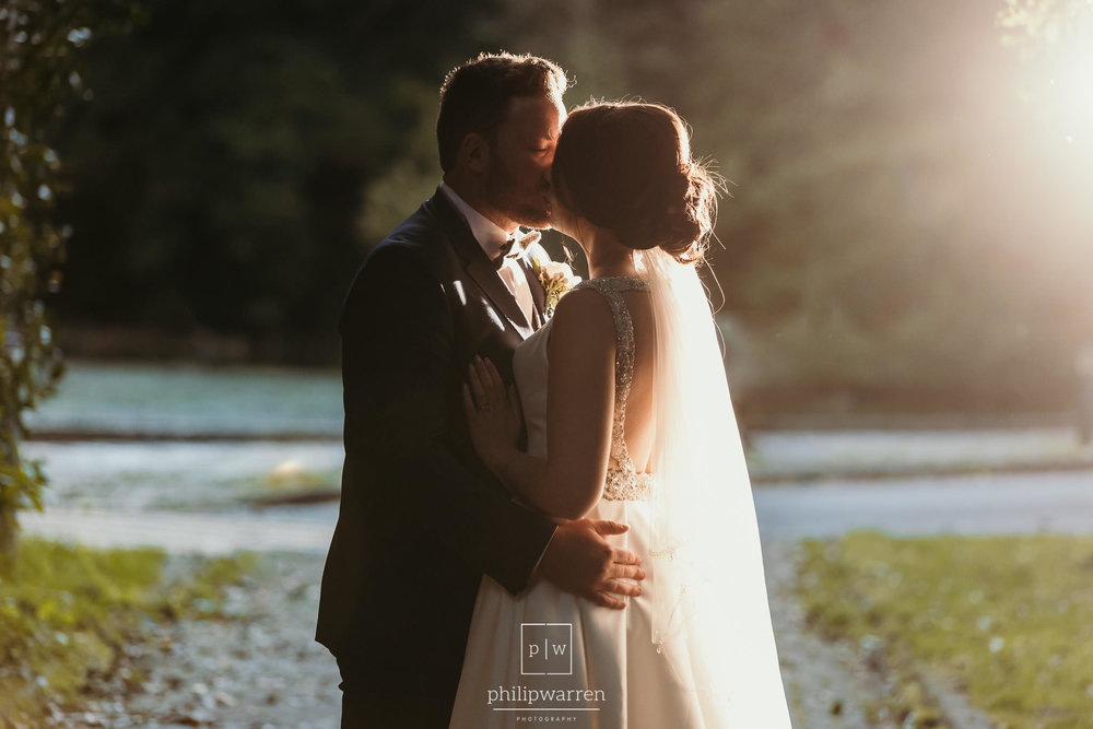 bride and groom kissing in evening sunlight
