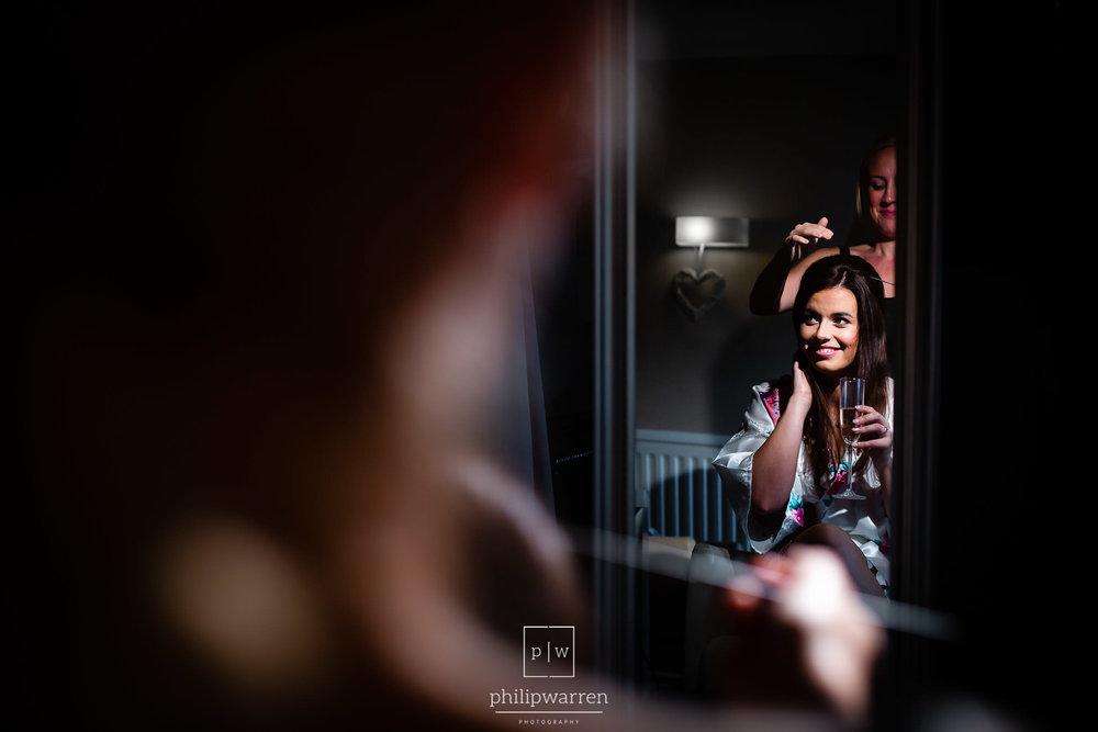bride having hair done before the wedding