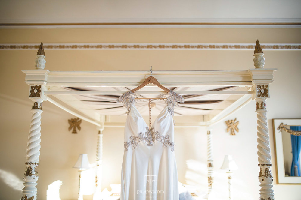 wedding dress hanging from four poster bed
