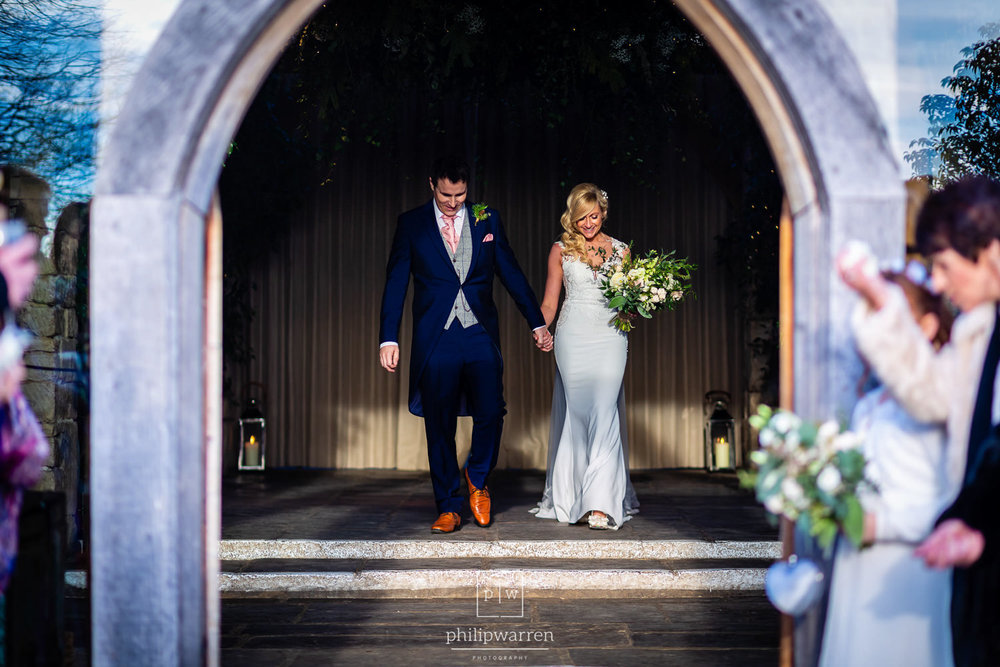 bride and groom exiting cripps barn