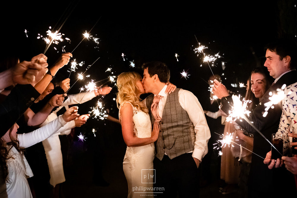 bride and groom kissing surrounded by sparklers