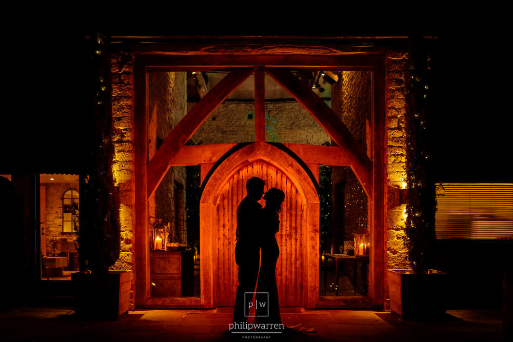 silhouette of bride and groom outside cripps barn