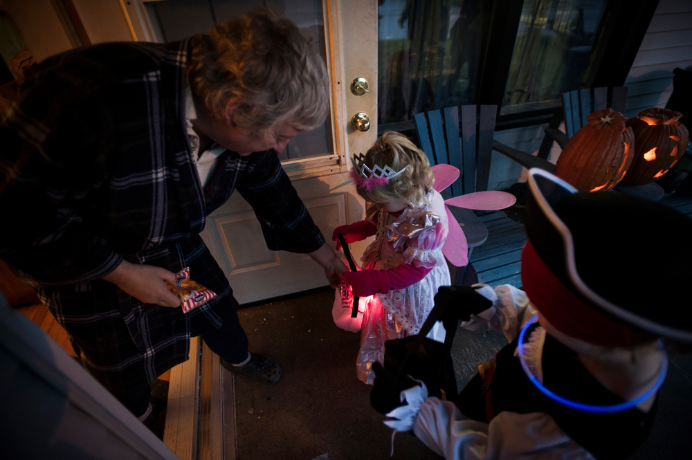 trick-or-treating  Mckenzie (C) collects candies from nearby neighbour in Frankford, Ontario.
