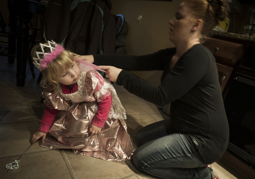 trick-or-treating  Randi (R) helps Mackenzie, 3, to put on her princess costume before heading out.