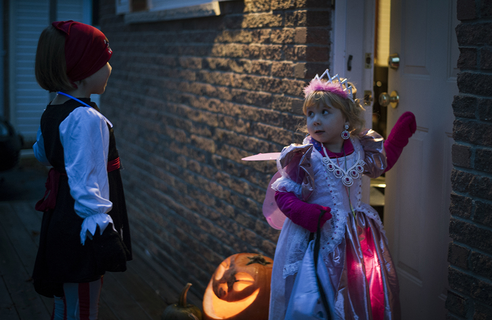 trick-or-treating  Mckenzie (R) looks at her sister, Madison, for encouragements before knocking on the door.