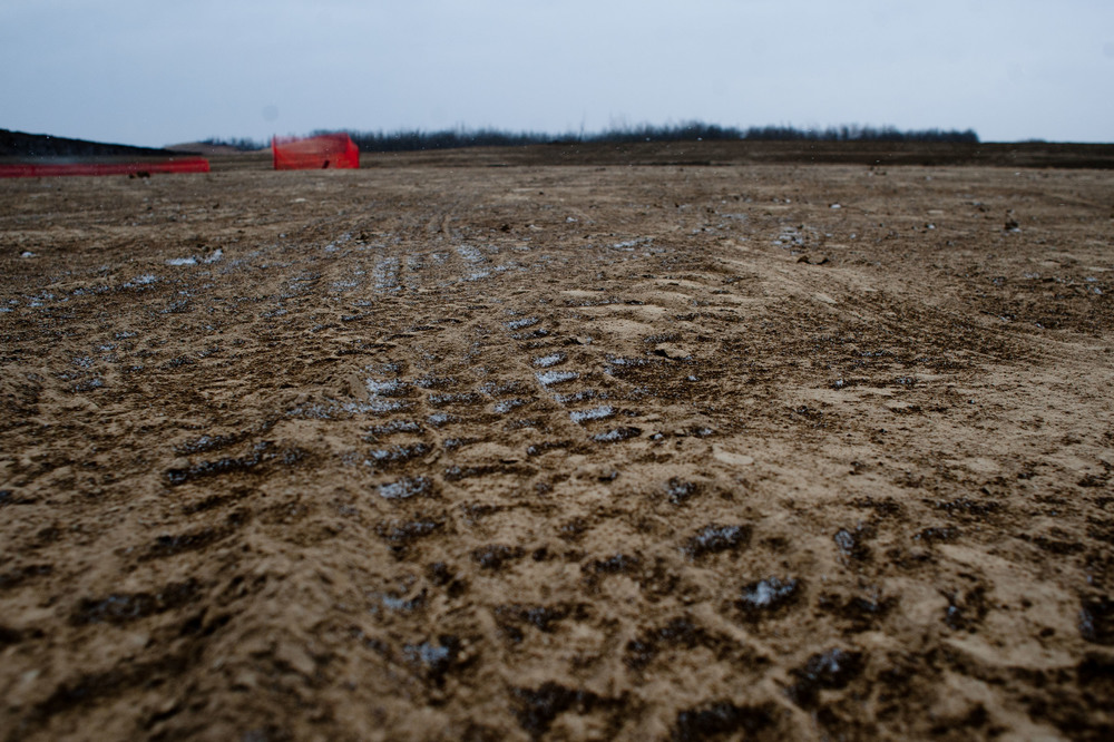 The tracks from all of the trucks are ground into the mud and half frozen.