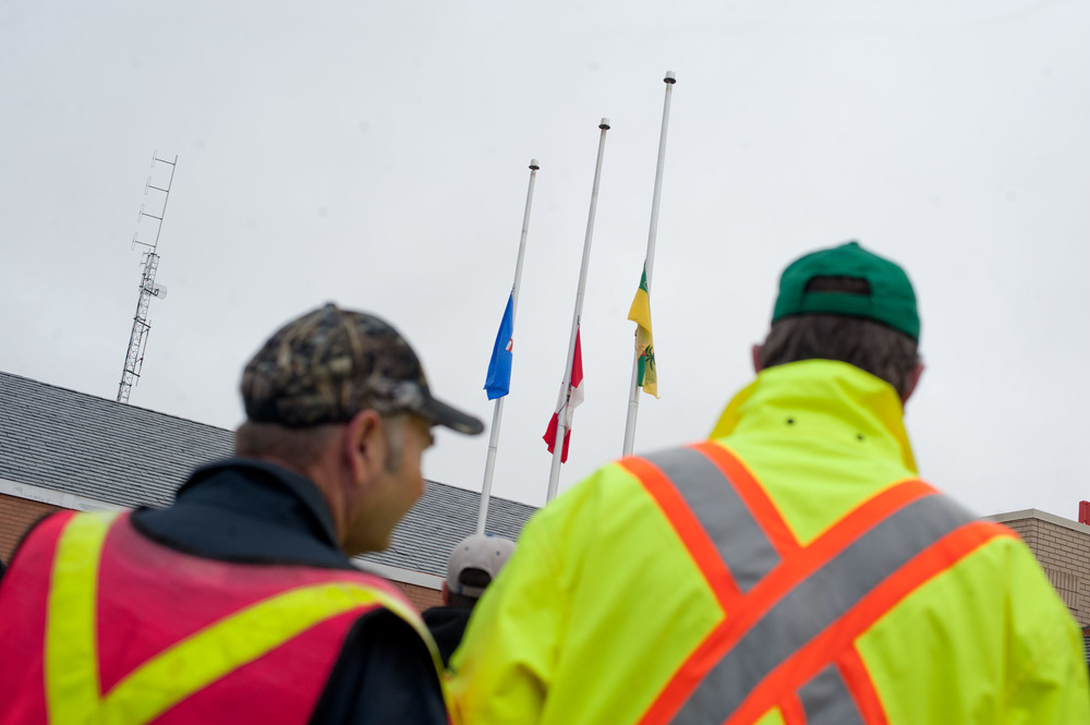 For National Day of Mourning there was a small ceremony at City Hall at around 9, and a lot of local workers and construction people were gathered to watch the flags be lowered to half-mast. I didn't want to have a photo of the mayor pulling at some rope, as I felt that would have missed the entire point of the event. Having two workers framing the flags made it work for me, and this shot ran front page.