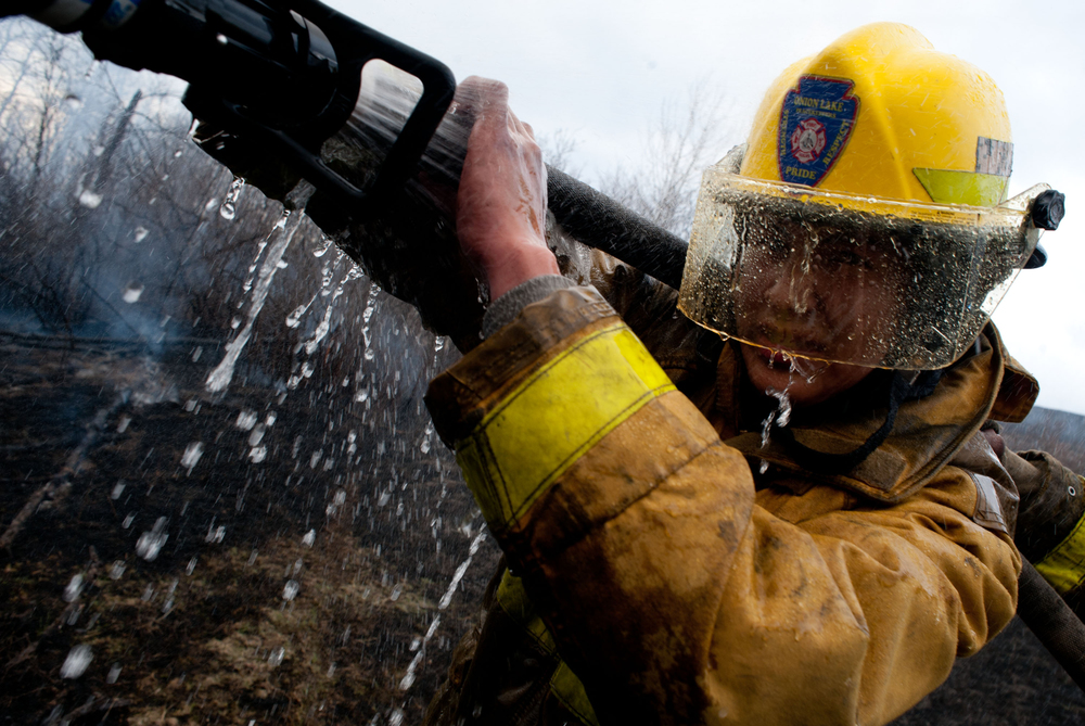 Young volunteer fire fighter David Muskego got his visor covered in water as he directed the high-pressure hose at the fire, which had been advancing through the dense brush and fallen trees nearer to the river.