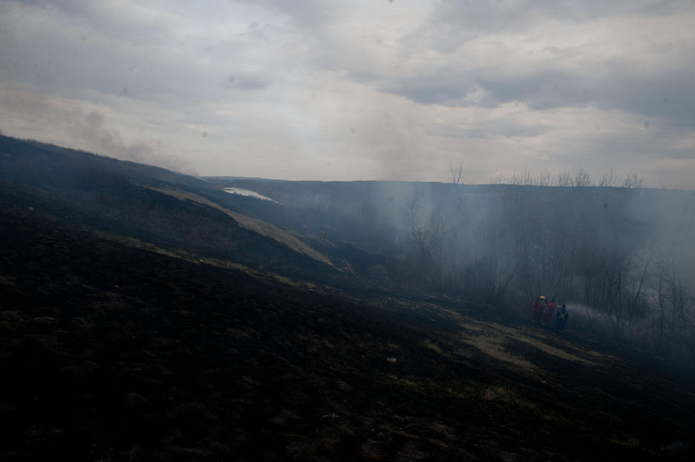 The smoking remains of the hillsides were scorched and blackened, with only small patches of untouched grass remaining.