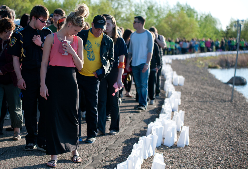 Marisa Johnson reads the names and phrases written on the luminaries that line the shore of the lake in Bud Miller Park. Friday May 30, 2014. James Wood/Lloydminster Meridian Booster/QMI Agency