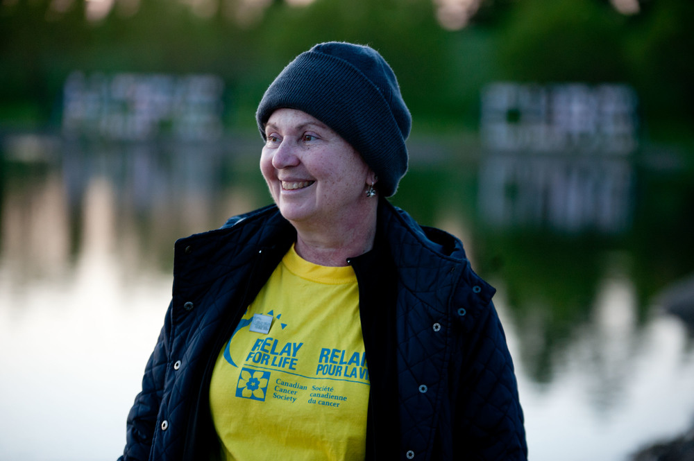 Survivor Elizabeth Kreiser is framed by twin signs along the shores of the lake in Bud Miller Park.Friday May 30, 2014. James Wood/Lloydminster Meridian Booster/QMI Agency