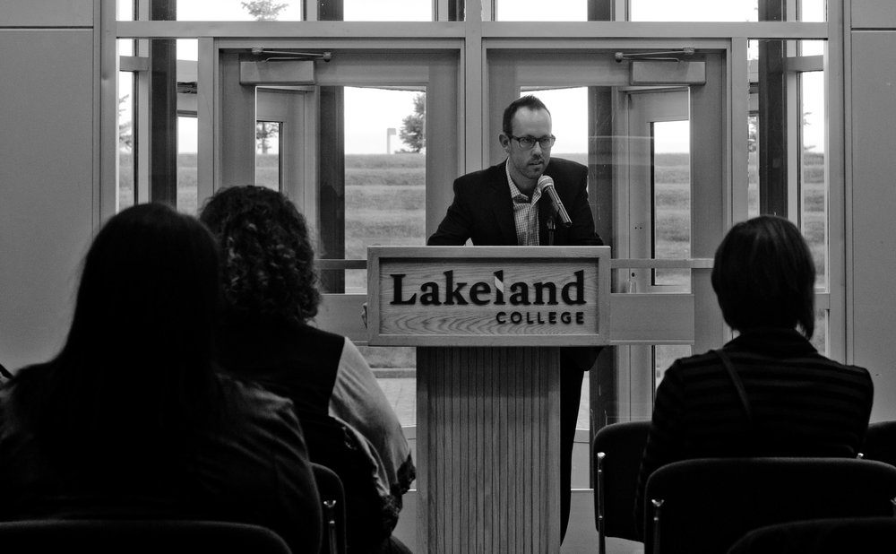 Shane Schneider, the co-founder of 100 Men Lloydminster, spoke at Whiting's event in September. Whiting announced his mayoral run at the local college, and Schneider spoke prior to Whiting taking the stage.