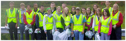 Volunteers pose in their clean-up vests at the side of the road.