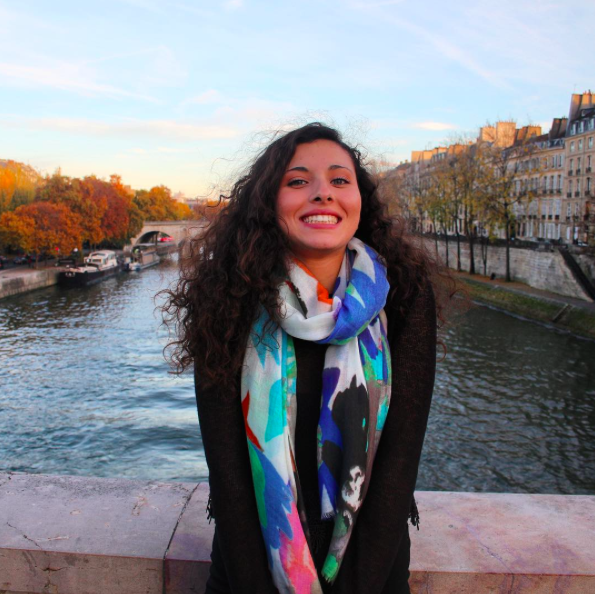 Salome smiling by the Seine in Paris, France Wearing: Big Flower Sheer Merino Wool Scarf