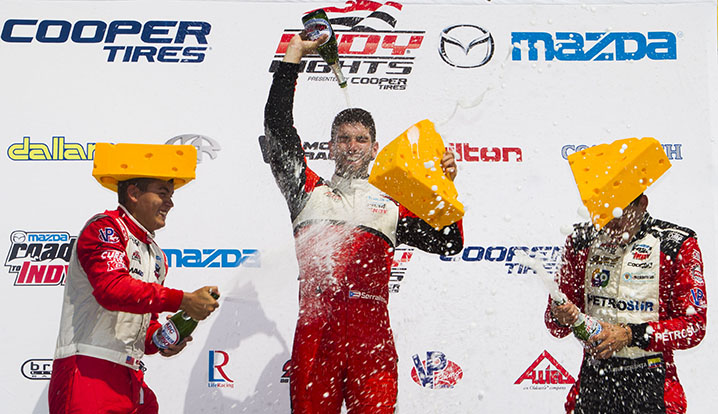 (From left to right) RC Enerson, second place, Felix Serralles, first place, and Juan Piedrahita, third place, celebrate with champagne after completing the Grand Prix of Milwaukee on Sunday, July 12, 2015 during Indy Fest.  The race was 100 laps on the Milwaukee Mile.