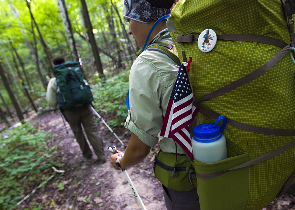 Natalie Koffarnus carries an American flag as she hikes behind Jenni Heisz on the Ice Age Trail as a part of the Warrior Hike Program on Thursday, July 16, 2015 in West Bend, Wi.
