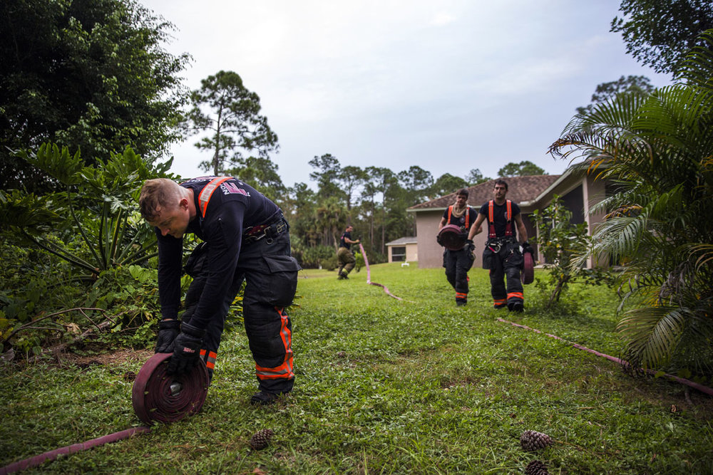 North Collier fire fighters work to pack up after putting out a house fire on Friday, October 28, 2016 in Golden Gate Estates. The authorities were called after a neighbor noticed the fire.