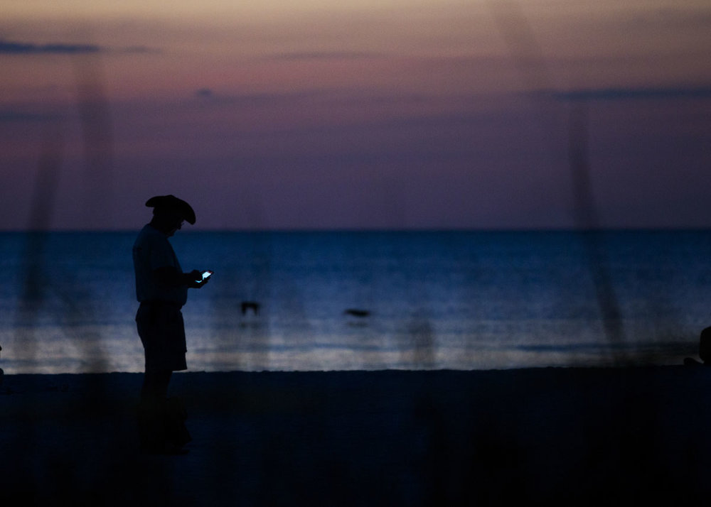 Martin Roddy, a volunteer sea turtle monitor, checks the time on his phone on Friday, October 31, 2016 at South Beach on Marco Island.  Roddy is one of the volunteers that checks this particular nest once every two hours.