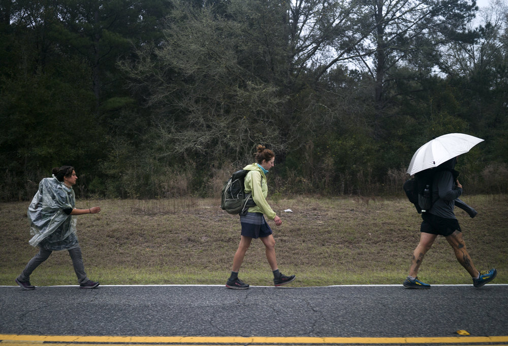 As it begins to rain near mile 718 of the trail, Cyrilia Trudel-Gazquez, Gretchen Matt, and Lint Bunting pull out their rain gear and continue hiking.