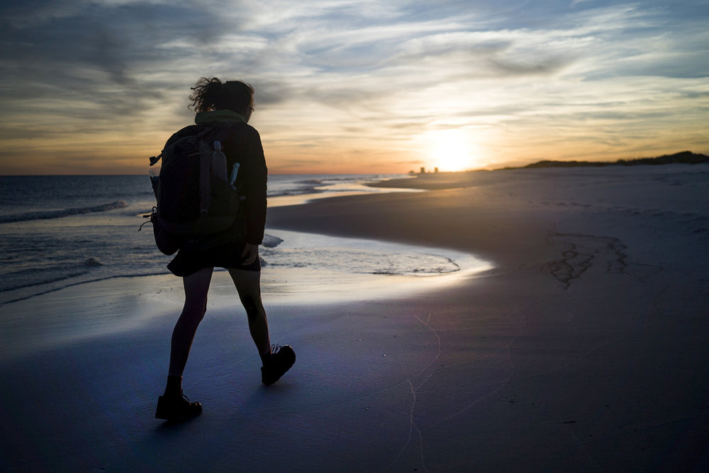 "Gretchen Matt hikes into the sunset along Pensacola Beach as she nears the end of her trip on Thursday, March 2, 2017. ""It felt like a strangely beautiful ending to such a challenging trip,"" said Matt."