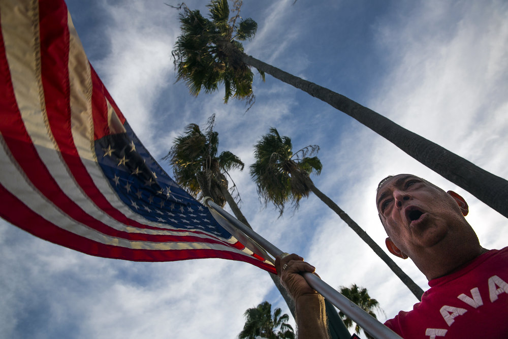 Pedro Blanco waves the Americn flag and cheers into the street on 5th Avenue South on Saturday, November 26, 2016 in the city of Naples. The Cuban community in Naples wished to celebrate the death of Fidel Castro.