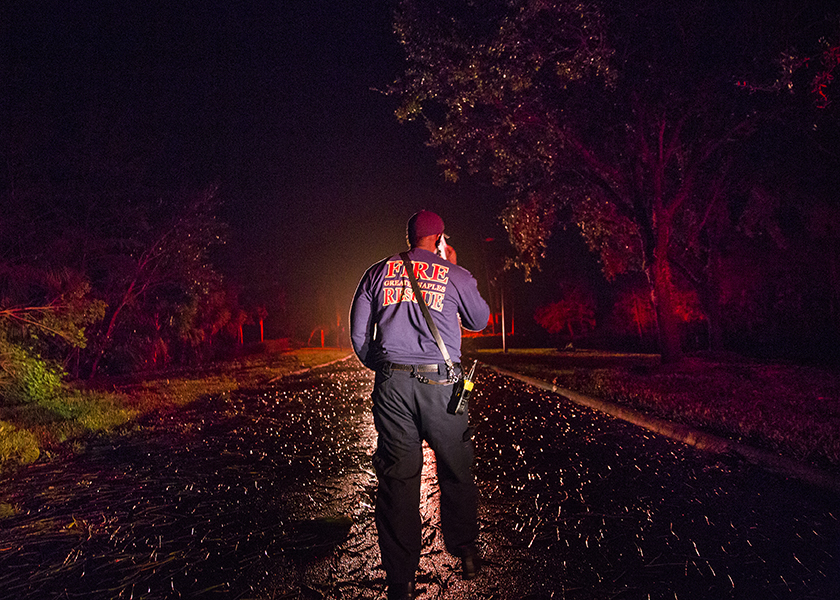 Torrence Andrews, firefighter with Great Naples Fire Rescue Station 72, peers down a road in the Forrest Glen community on Sunday, September 10, 2017 after Hurricane Irma passed and the company was cleared to assess roads for obstructions. The vehicle Rescue 72 became stuck on a median when trying to go around a fallen tree in the road and needed to call to the station to be pulled out.