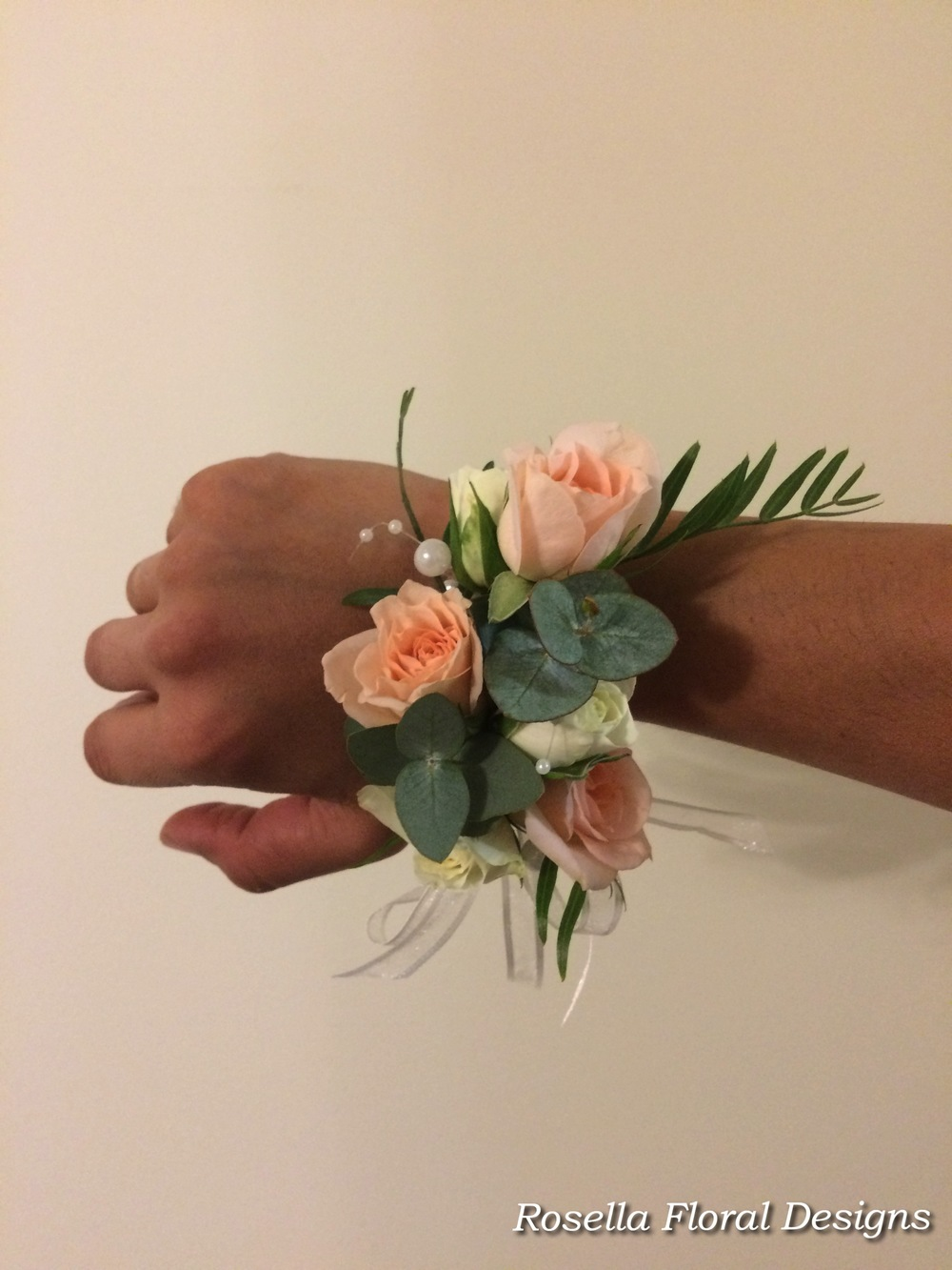 Wrist corsage peachy colour roses and gum.jpg
