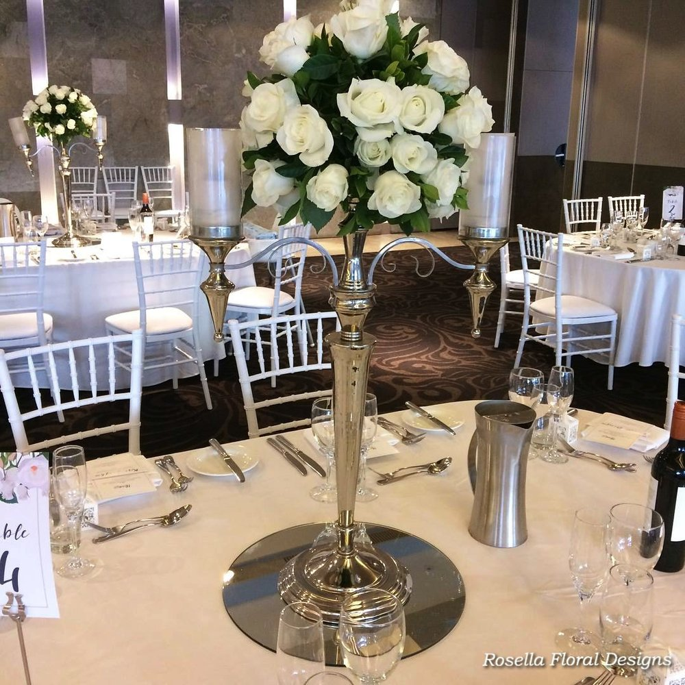 Silver candelabra with white flowers roses and foliage .jpg