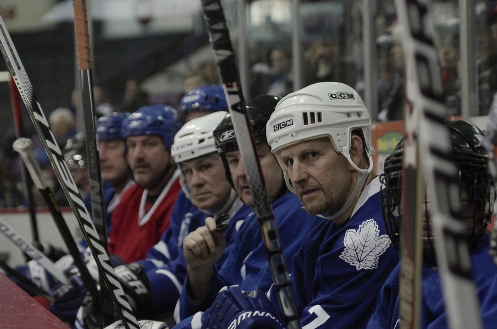 Gary Roberts (far right) rests on the bench during a charity match in Brampton at the Powerade Centre on February 9, 2015.  Other NHL Alumni present included Gilbert Dionne (in red) and Rick Vaive (centre, white helmet).  As published in Snapd Brampton, March 2015.