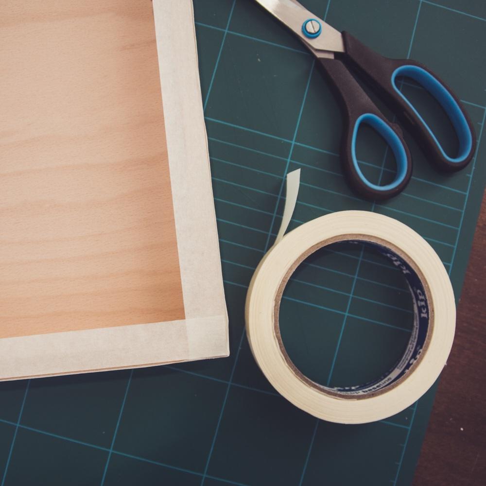Der Holzrahmen wird mit Malerkrepp abgeklebt