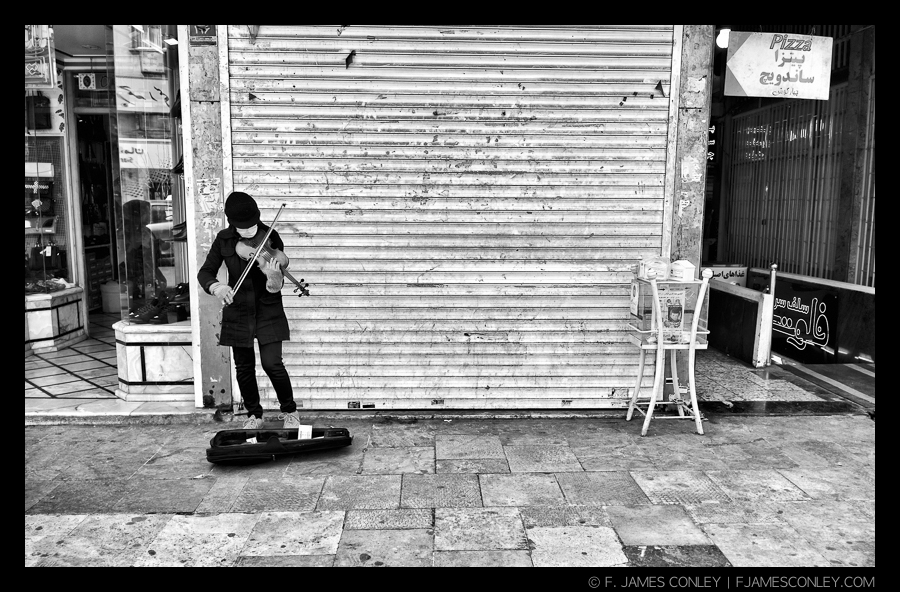 Some scenes seem ordinary, until you understand the context. In most countries, public musicians are common. In Iran, this woman was risking her life not only from the authorities, but from passers-by. She is gloved and masked to protect her from attack, and she didn't remain here for very long. Her choice to play the violin on the street wasn't simply artistic expression: it was a political statement with very high risk.