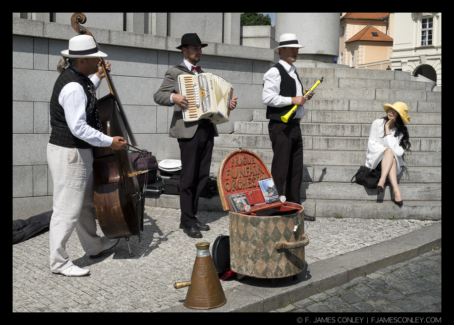 The stylish woman in the yellow hat gets her own serenade in Prague from a group of guys dressed to support their style of music.