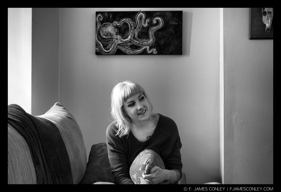 The subject in her own space, with an octopus she painted, gives the spectator context for the portrait.