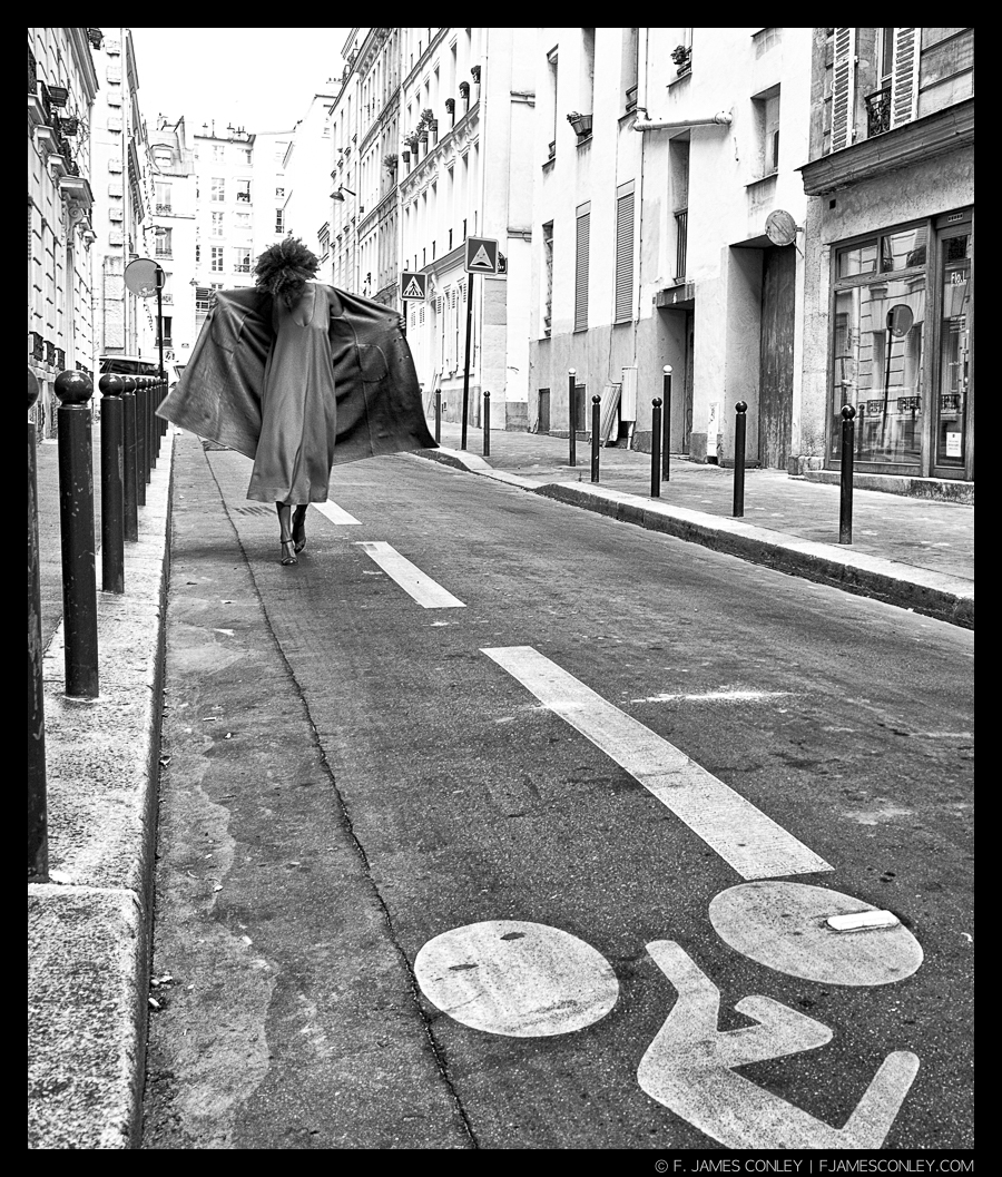 Not a pose. In this shot, Rayanne had turned the reversible coat inside out and was putting it back on. It was a brief moment of action on a poorly lit Parisian street. Without live exposure compensation on the XE-1, the image wouldn't exist.