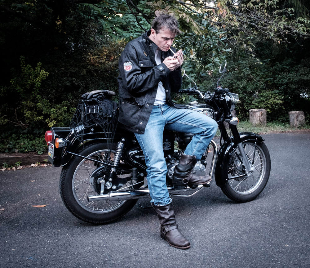 A rare image of James and one of his Royal Enfield bikes, featuring the Ride&Sons Escape Waxed Cotton Jacket.