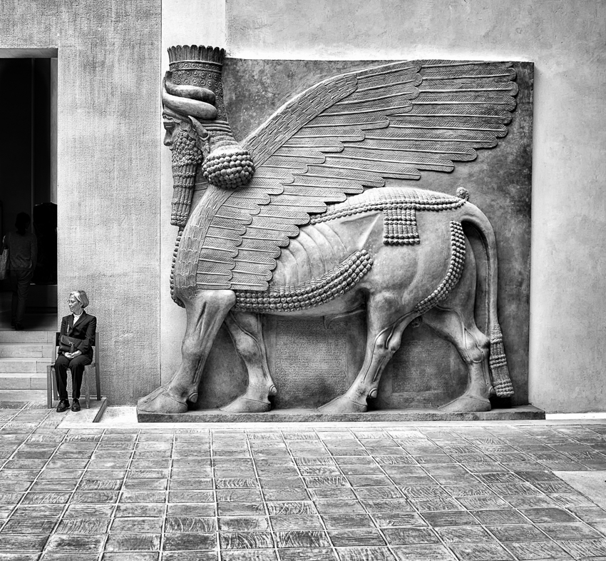 A Lamassu, dated at 1100 years BC, quietly approaches a woman in the Salle du Code de Hammurabi Mesopatami in the Louvre.